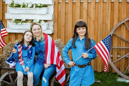 Beautiful woman and two girls spend time on the street, on the background of the flag of America. Independence Day