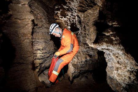 Man walking and exploring dark cave with light headlamp underground.