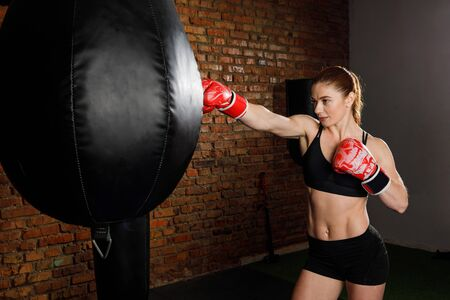 Fit strong brunette woman in sportswear top and shorts fights a punching bag with boxing gloves in the gym. Healthy Lifestyle