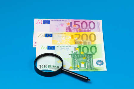 Euro banknotes and magnifier on a blue background Banque d'images