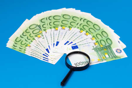 Euro banknotes and magnifier on a blue background Imagens