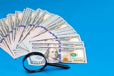 Dollar banknotes and magnifier on a blue background