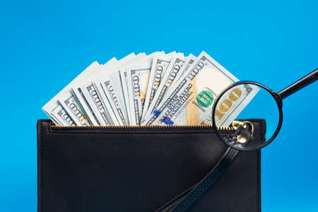 Black wallet with one hundred dollar bills on a blue background