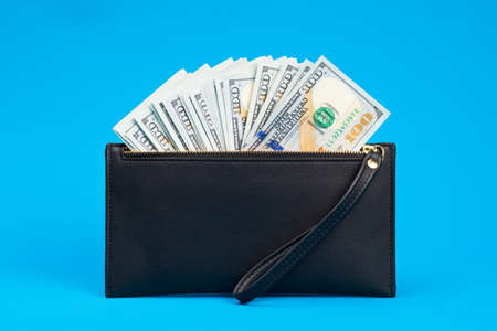 Many hundreds of dollars looks out of a black leather wallet on a blue background.