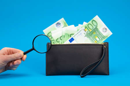 100 euro bills and magnifying glass with black wallet. Concept of counterfeit money.