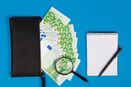 100 Euro bills and magnifying glass with black purse and notepad. Concept of counterfeit money.