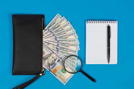 100 US dollars bills and magnifying glass with black purse and notepad. Concept of counterfeit money