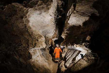 Speleologist descend by the rope in the deep vertical cave tunnel.