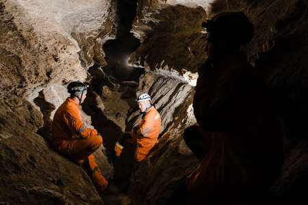 Three men, strong physique, explore the cave. Men dressed in special clothes to pass through the cave and stopped, looking at the map.