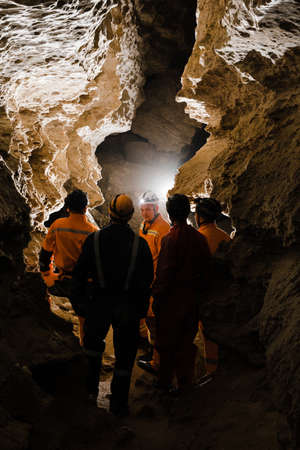 Five men, strong physique, explore the cave. Men dressed in special clothes to pass through the cave and stopped, looking at the map. Imagens
