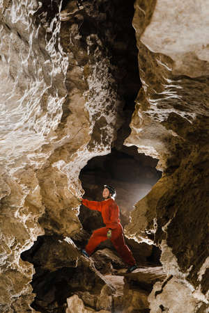 A portrait of a young female caver exploring the cave. Imagens