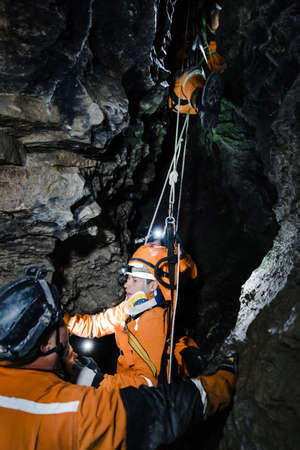 Cave rescuer helping injured climber