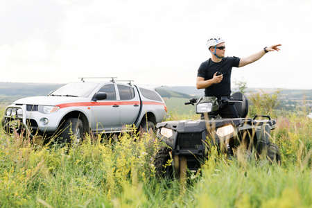 The rescuer, a beautiful athletic physique, rides an ATV in the middle of the field. Imagens