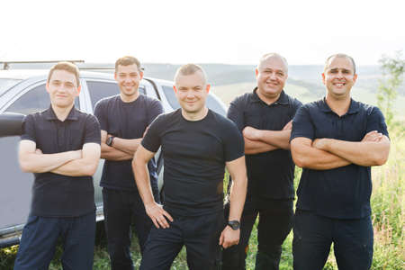 A team of courageous rescuers in black uniforms standing in a field