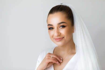 Morning of the bride in a white robe and a veil in the room