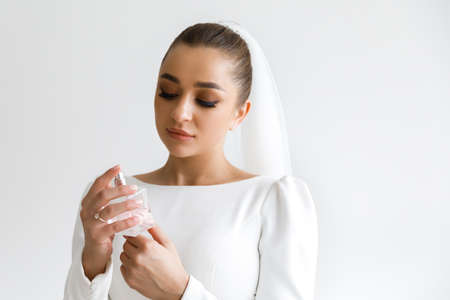 Beautiful luxurious bride holding a bottle of perfume Imagens