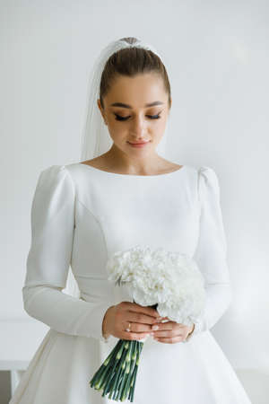 Bride in beautiful dress standing indoors interior at home. Trendy wedding style shot. Wedding makeup and hairstyle. Beautiful Bride in the morning.