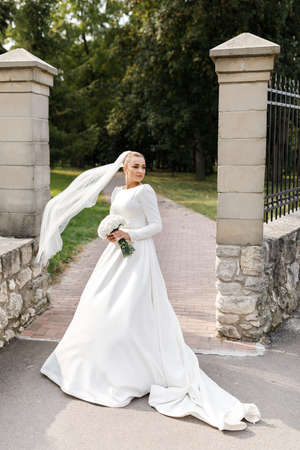 Portrait of a beautiful blonde bride with flowers in park