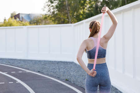 Young sportive woman doing exercises with elastic band outdoor.