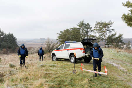 Emergency workers work outdoors. A man in uniform works with a metal detector