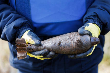 A man in a special suit works with a detector and found an explosive device. Banque d'images