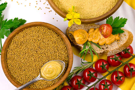 Yellow mustard flour in ceramic bowl, mustard seeds in awoden bowl, red cherry tomatoes, parsley, rosemary branch and slice of bread with mustard isolated on white background. Healthy food concep