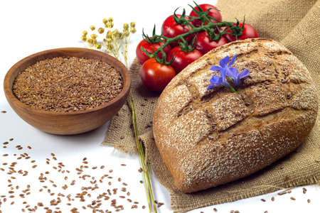 Flax or linen seeds in a bowl, flax dry herbs, bread and cherry tomatoes on linen cloth Stock fotó
