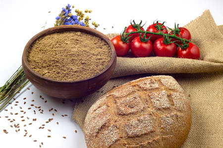 Flax or linen flour in a bowl, flax dry herbs, bread and cherry tomatoes on linen cloth
