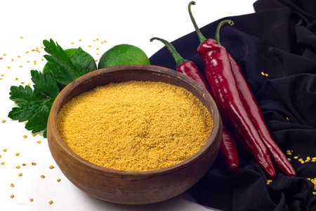 Red chili pepper on black cloth, chili flour in ceramic bowl, greenlimes and parsley isolated on white background 免版税图像