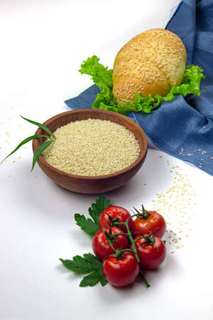 Sesame seeds in ceramic bowl, bread crescent, lettuce salad and tomatoes isolated on white background