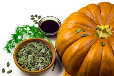 Ripe orange pumpkin, pumpkin seeds in a wooden bowl, pumpkin oil in a glass cup, cucumber and fennel isolated on white background. Healthy food concept