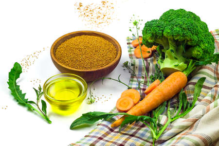 Camelina sativa seeds in a wooden bowl, camelina oil in a glass dish, carrot and broccoli isolated on white background. Healthy food concept