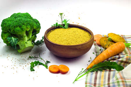 Camelina sativa flour in ceramic bowl, cookies, carrot and broccoli isolated on white background. Healthy food concept Фото со стока