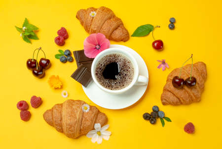 French croissants, cup of coffe, dark chocolate, flowers and berries on yellow background top view