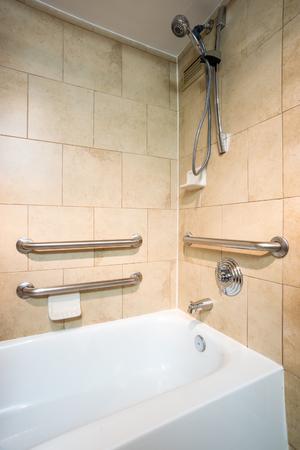 Accesso per disabili Vasca da bagno in una stanza d'albergo con barre a mano afferrate
