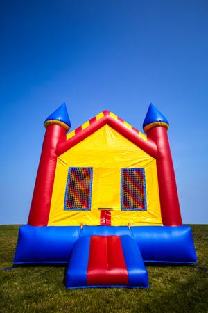 庭で子供膨張弾む城家。 写真素材
