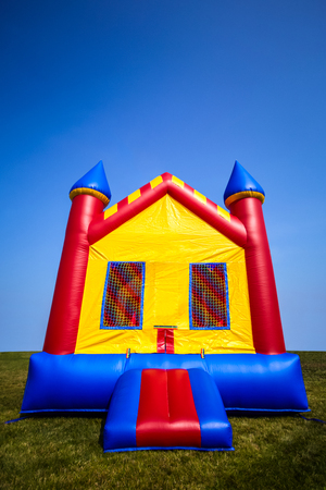 Children's inflatable bouncy castle house in a yard.