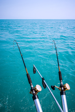 fishing rig: Picture of a two fishing poles over turquoise colored water and a blue sky