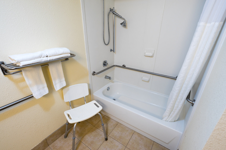 Disabed Access Bathroom With Shower Bathtub Hand Rails And A Chair Stock  Photo   77741984