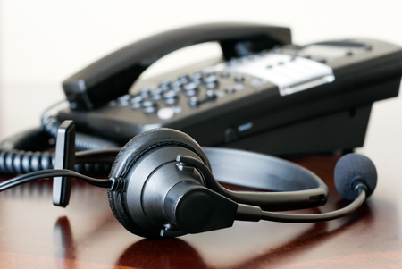 earpiece: Phone headset and business telephone on an office desk