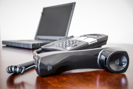 Picture of a black business telephone with its receiver off the hook and a laptop computer on a brown office desk 写真素材