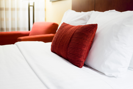 Hotel room bed pillows and chair in a modern hotel