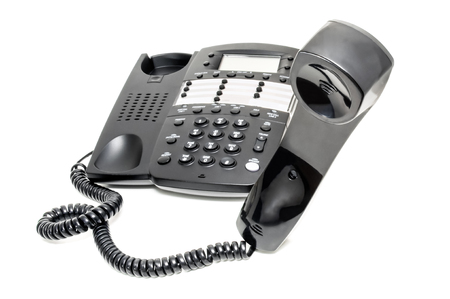 touchtone: Black business landline telephone with its receiver off of the hook on a white background. Stock Photo