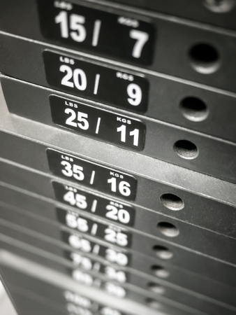 Healthclub weight plates on gym workout equipment
