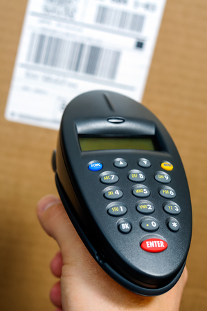 Barcode scanner reader being held by a person's hand scanning a UPC label on a box