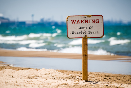 Picture of a wooden warning sign in the sand at the beach indicating the limit of lifeguard patrol coverage.