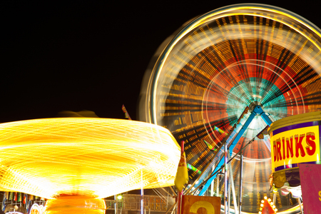 Carnival Rides - Picture of carnival rides and ferris wheel at night motion-blurred.