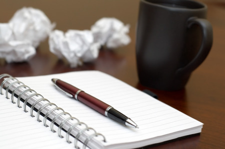 Writers Block picture. Scene of writers block with a notepad, pen, and several pieces of paper crumpled up into balls.