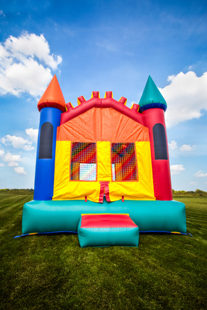 Inflatable bounce castle house in a large open yard.