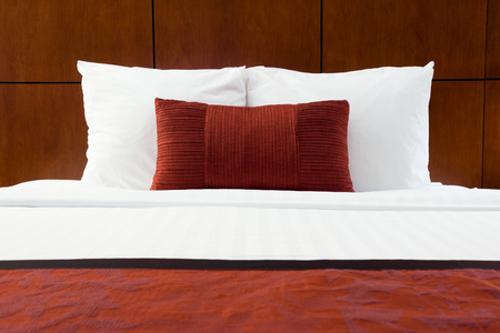 upscale: Hotel room bed, red pillows, and wood headboard at an upscale hotel